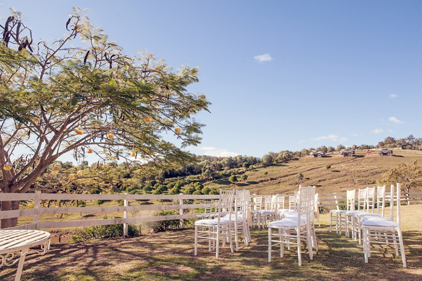 Ceremony features white Tiffany chairs